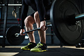 Active young man training with barbell in gym