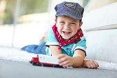 A cute little boy lying on the livingroom floor and playing with a toy train