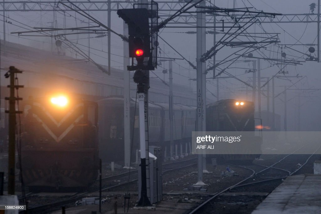 Trains arrive during a cold and foggy morning at a railway station in Lahore on December 31, 2012. Ongoing foggy weather in Punjab and other parts of the country has badly affected flight and rail schedules. AFP PHOTO/ARIF ALI