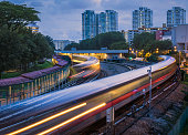 Mass Rapid Transit (MRT) trains arriving and leaving the station of Ang Mo Kio in Singapore. The image was taken in the evening during blue hour and the trains have motion blur.
