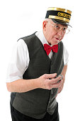 A senior conductor holding his pocket watch while looking for the train.  On a white background.