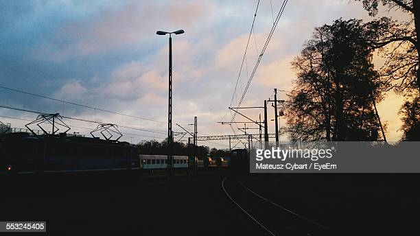 Trains On Track Against Cloudy Sky
