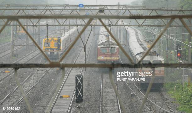 Trains run slow during heavy rain showers in Mumbai on September 20 2017 Dozens of flights were diverted from Mumbai after a SpiceJet plane overshot...