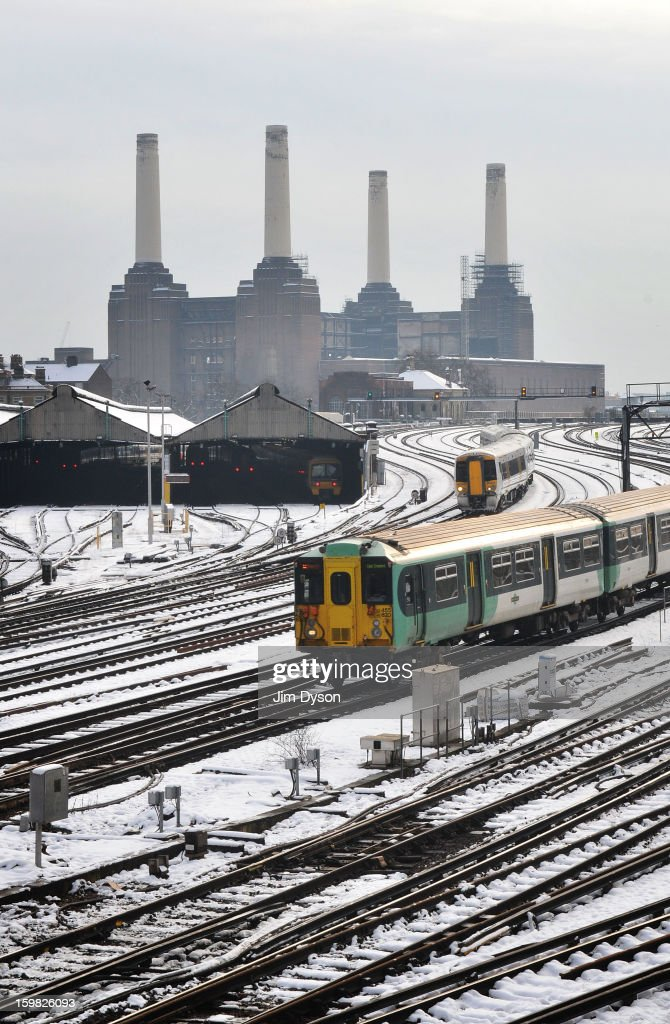 Trains travel in and out of Victoria station in front of Battersea Power Station on January 21, 2013 in London, United Kingdom. The United Kingdom has suffered a weekend of heavy snowfall with transport routes affected including the cancellation of many rail services.
