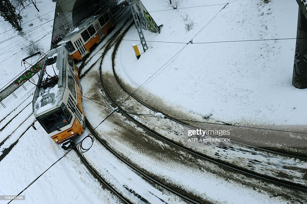 A tram approaches a station of Budapest, 12th district on January 14, 2013 as the Hungarian capital and several counties were hit by about 20 cm snow last night and this morning. The heavy snowfalls caused chaos in traffic and public transport. AFP PHOTO / ATTILA KISBENEDEK
