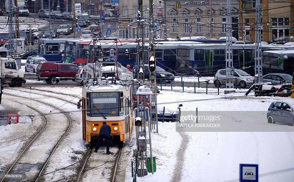 A tram driver cleans a rail converter in Budapest, on January 14, 2013 following a snowfall.