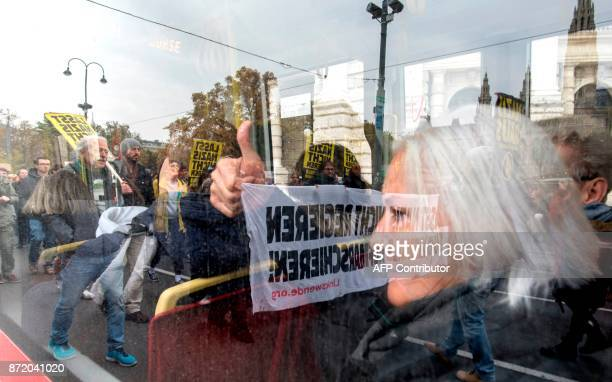 A tram passenger gives a thumb up to antifascist demonstrators marching towards the Austrian parliament on November 9 2017 in Vienna to protest...