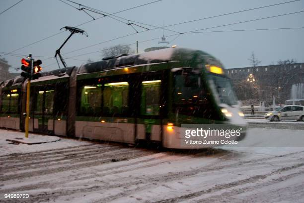 A tram passes as it snows on December 21 2009 in Milan Italy Snow storms and sub zero temperatures have swept across Europe causing disruption on...