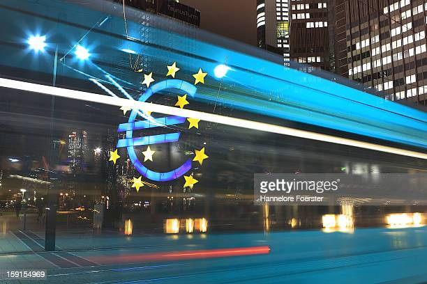 A tram passes the giant Euro symbol outside the headquarters of the European Central Bank on January 8 2013 in Frankfurt am Main Germany The...
