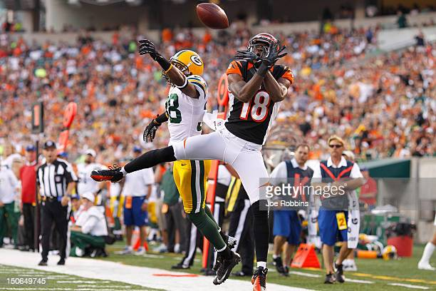 Tramon Williams of the Green Bay Packers defends a pass in the end zone against AJ Green of the Cincinnati Bengals during a preseason NFL game at...