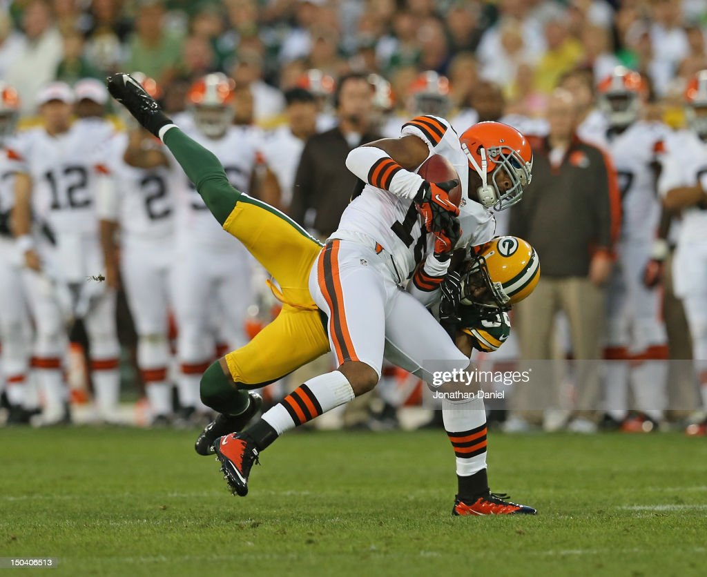 Tramon Williams of the Green Bay Packers tackles Joshua Cribbs of the Cleveland Browns during a preseason game at Lambeau Field on August 16 2012 in...