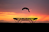 silhouetted teenager jumping on trampoline in sunset