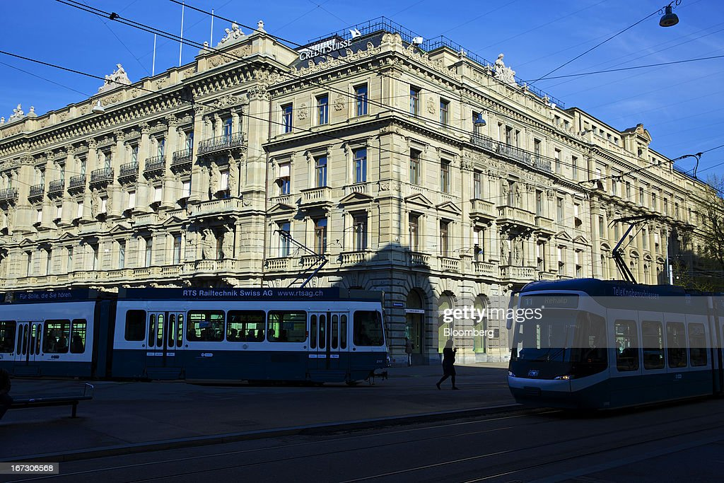 Trams pass the headquarters of Credit Suisse Group AG in Zurich, Switzerland, on Wednesday, April 24, 2013. Credit Suisse Group AG, the second- biggest Swiss bank, posted a jump in first-quarter profit as year-earlier charges related to its own debt and bonus payments weren't repeated. Photographer: Gianluca Colla/Bloomberg via Getty Images