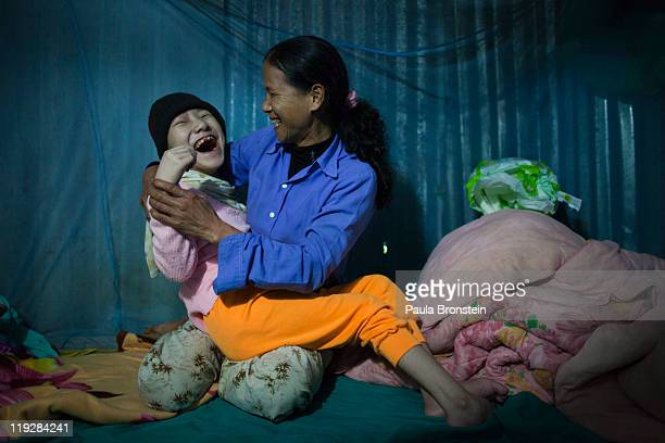 Tran Thi Nghien laughs with her handicapped daughter Hung at their home March 8 in Cam Lo in Quang Tri province Vietnam Many of the families have had...
