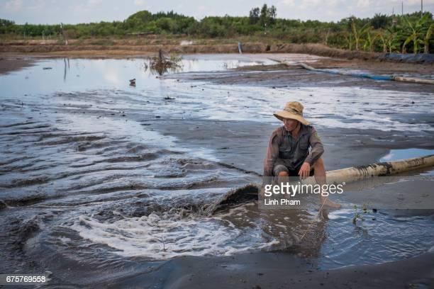 Tran Van Tam pumps salt water into his piece of land to turn it into a shrimp farm in Thua Duc Village Binh Dai District Ben Tre Province Vietnam The...