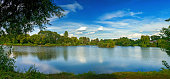 Tranquil landscape at a lake, with the vibrant sky, white clouds and the trees reflected in the clean blue water