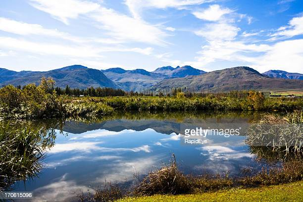 Tranquil river reflects mountains and sky