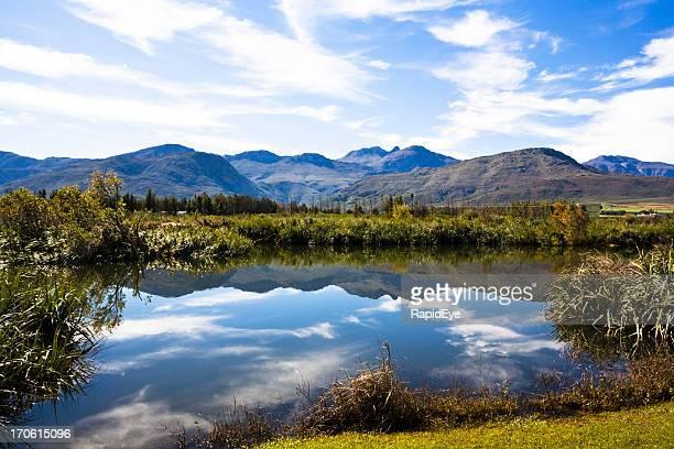 Paisible rivière reflète les montagnes et le ciel