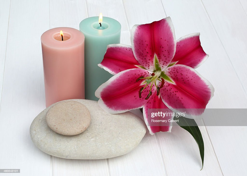 Tranquil still-life - lily, candles and pebbles.