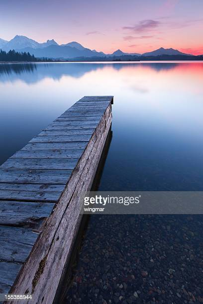 tranquil sunset at lake bannwaldsee with jetty, bavaria - germany