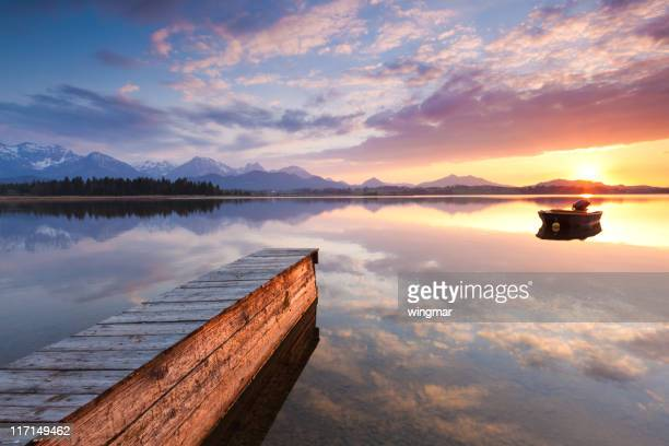 Paisible coucher de soleil sur le lac avec ponton hopfensee, Bavière, en bateau, en Allemagne