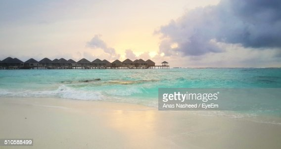 Tranquil view of beach with stilt houses against cloudy sky