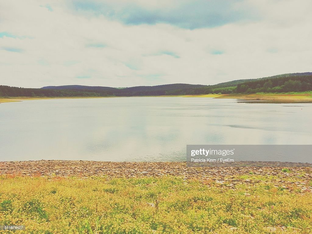 Tranquil view of lake against cloudy sky