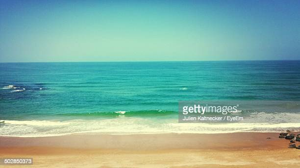 Tranquil view of turquoise sea at beach against clear sky