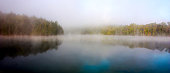 Canoe camping on a tranquil lake on an island overlooking a beaver pond.