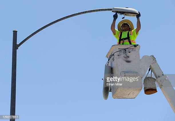 TransCore's Danny Downs removes a street light to replace it with a new LED light fixture August 1 2011 in Las Vegas Nevada The new energyefficient...