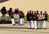 Transfer cases are carried into a hangar during the Transfer of Remains Ceremony for the return of Ambassador Christopher Stevens and three other...