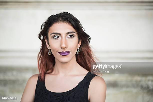 Transgender female in black top, looking away