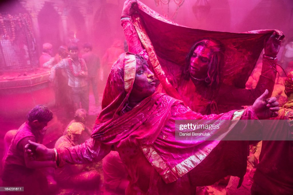 Transgender Hindu devotees dance as others play with color during Lathmaar Holi celebrations on March 21, 2013 in the village of Barsana, near Mathura, India. The tradition of playing with colours on Holi draws its roots from a legend of Radha and the Hindu God Krishna. It is believed that young Krishna was jealous of Radha's fair complexion since he himself was himself very dark. After questioning his mother Yashoda on the darkness of his complexion, Yashoda, teasingly asked him to colour Radha's face in which ever colour he wanted. In a mischievous mood, Krishna applied colour on Radha's face. The tradition of applying color on one's beloved is being religiously followed till date.