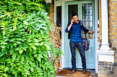 Transgender male at the door talking on mobile phone