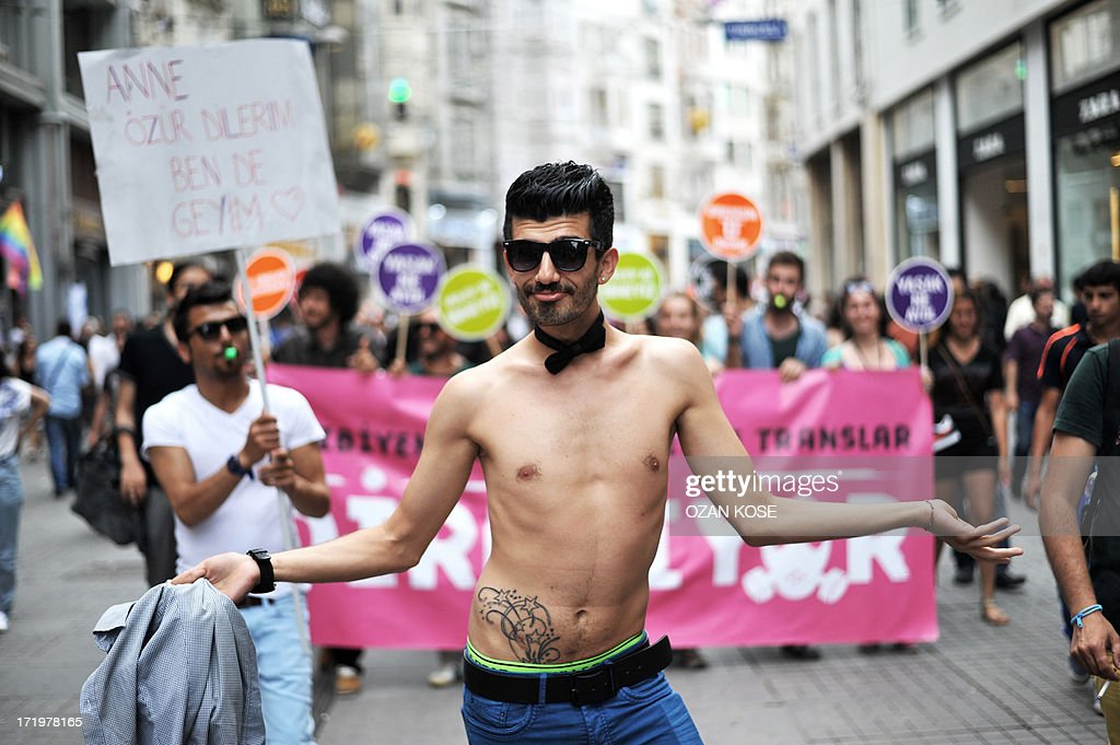 A transgender man takes off his clothes during a gay parade on Istiklal Street, the main shopping corridor on June 30, 2013 in Istanbul during the fourth Trans Pride Parade as part of the Trans Pride Week 2013, which is organized by Istanbul's 'Lesbians, Gays, Bisexuals, Transvestites and Transsexuals' (LGBTT) solidarity organization.