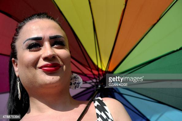 A transgender person looks on with an rainbow umbrella during a Gay Pride parade on June 28 2015 in the Istiklal street near Taksim square in...