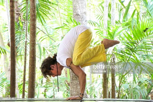 Transgender yogini practicing on wooden platform