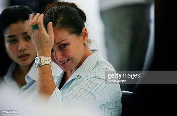 Translator Eka Sulistiowati sits with Australian Schapelle Corby as she cries while listening to Prosecutor Ida Bagus Wisnawantu announcing the...