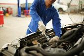 Cropped image of mechanic checking car transmission