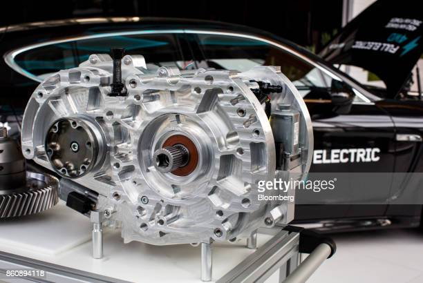 Transmission gear components sits beside a modified electric Porsche AG Panamera automobile at the Kreisel Electric GmbH research center and battery...