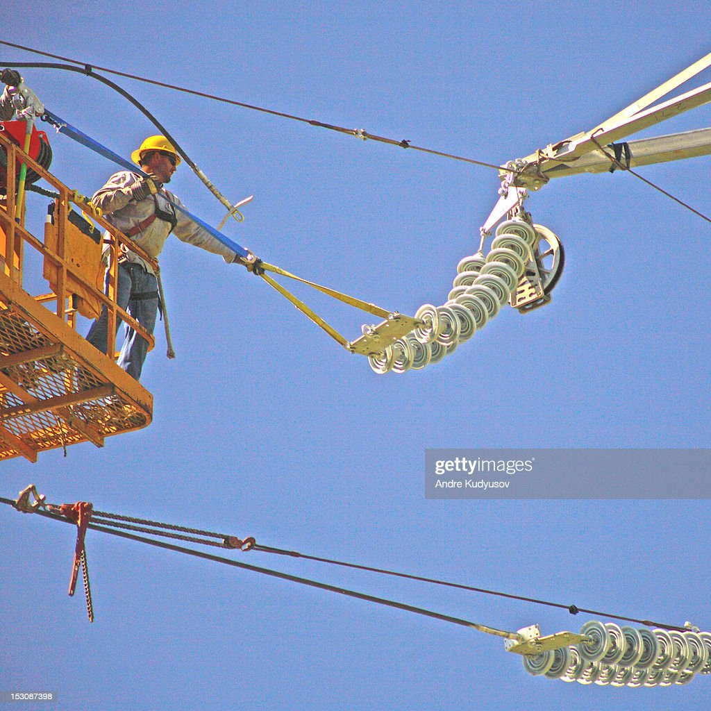 Transmission lineman at work : Stock Photo