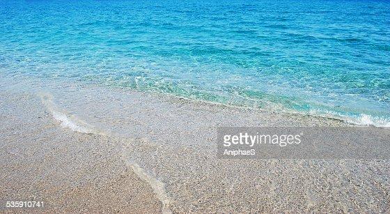 Transparente onda azul oscuro de ea que se divide en la playa : Foto de stock