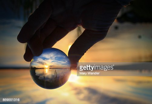 Transparent glass ball reflecting a sunset on the lake : Stock Photo