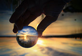 Fingers holding transparent glass ball reflecting the sunset on the water of Cold Lake, Alberta