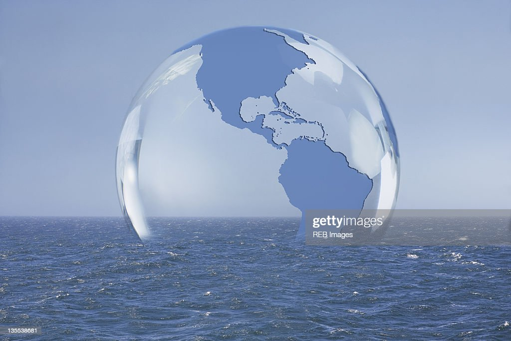 Transparent globe floating on ocean : Stock Photo