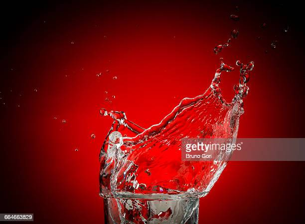Transparent liquid and droplets splashing against red background
