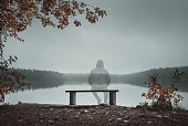 A transparent man is sitting on a bench and looking at the lake. Back view. Foggy morning. Autumn theme