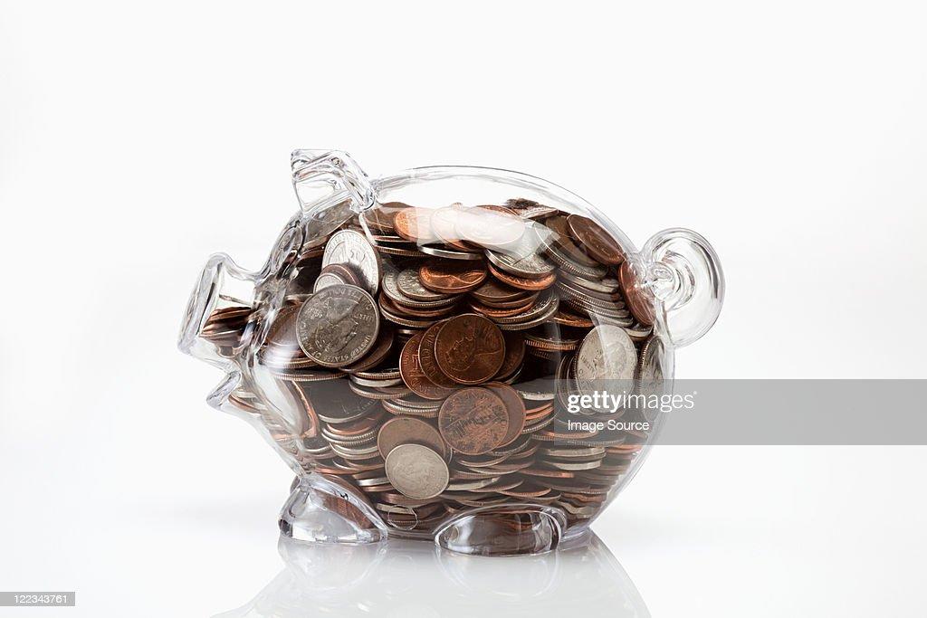 Transparent piggy bank full of coins