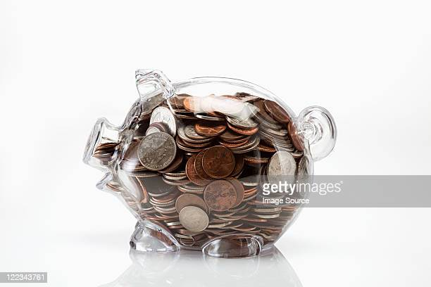 Transparent piggy bank full of coins