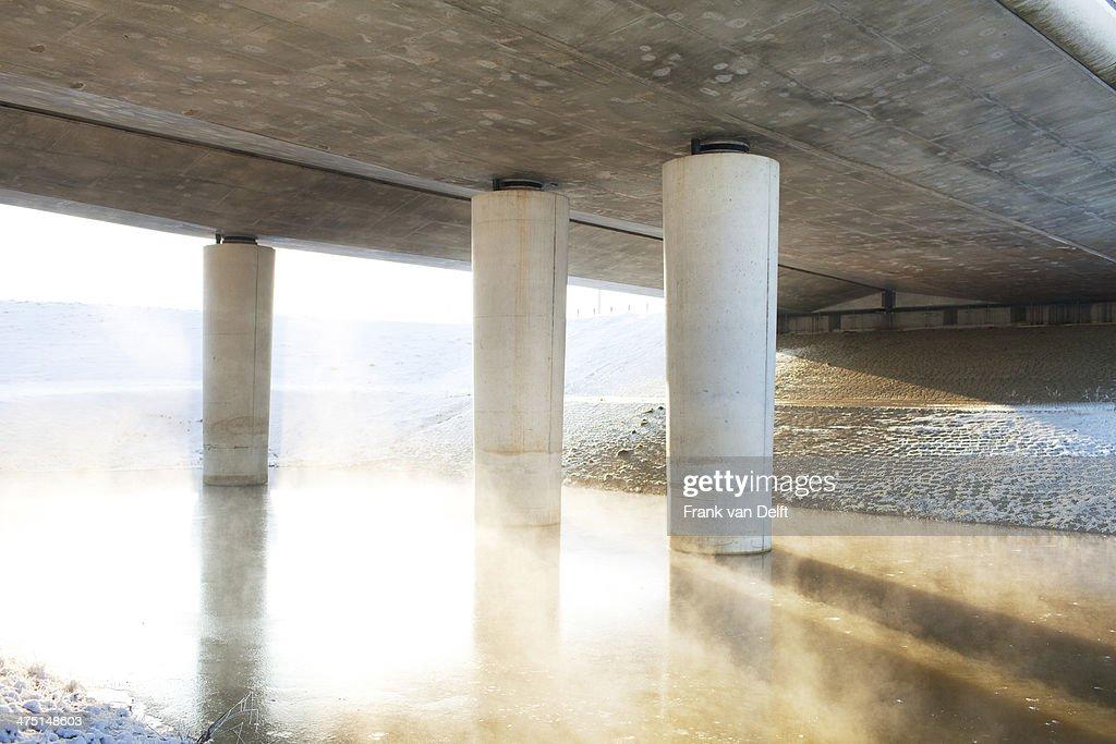 Transport bridge over misty river in winter